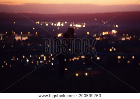 Close-up of loving couple dancing against background of night sky with stars, in background night city - bokeh blurred. Concept first love, kiss, Valentine's Day. copyspase