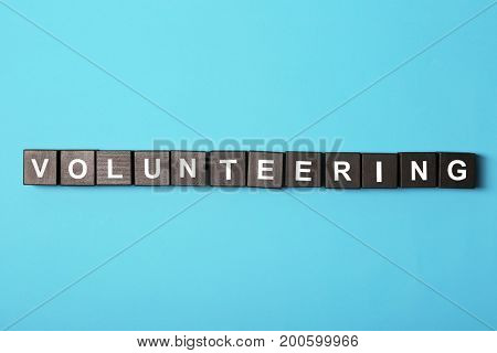 Volunteering concept. Wooden cubes on color background