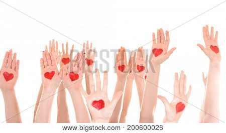 Raised in air hands with drawn hearts on palms against white background. Volunteering concept