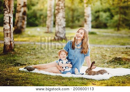 Mother with a young child boy rejoice, laugh in the park and play with rabbits. Concept happy childhood, friendly family, happiness, first acquaintance. copyspace