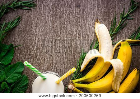 Banana smoothie and fresh banana on wooden table. Top view. Copy space. Flat lay. Still life