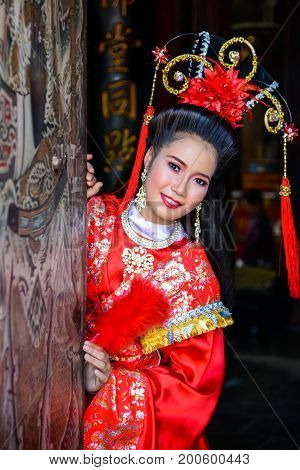 Chachoengsao Thailand - July 14 2013 : Beautiful woman with traditional chinese red dress at Chinese shrine entrance in Thailand.