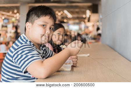 Obese brother and sister eating box lunch in food court fastfood concept