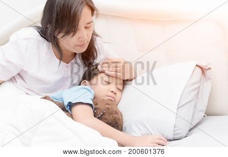Sick girl laying in bed and mother hand taking temperature. Sick child with fever and illness in bed healthcare concept