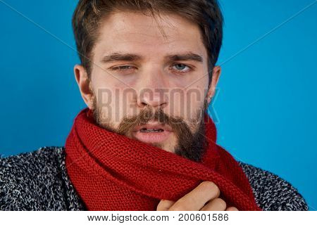 Man with a beard on a blue background in a scarf, portrait, illness, sick, flu, emotions.