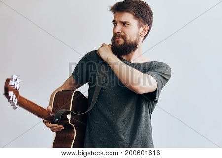 Man with a beard on a light background in headphones holds a guitar, musical instruments.