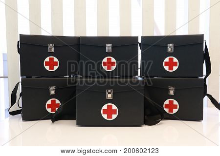 Group of first aid box in first aid room in hospital. Black first aid medical kit preparing for emergency in school first aid room. First aid box for background.