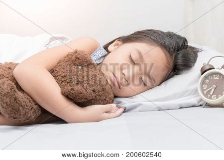 Cute Little Asian Girl Sleep And Hug Teddy Bear On Bed