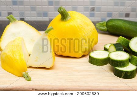 Pati pan courgette Yellow zucchini or pati pan courgette on a wooden board