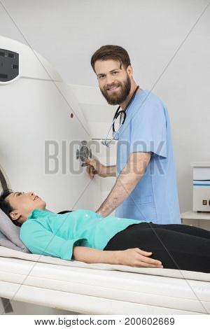 Young Doctor About To Start CT Scan On Female Patient