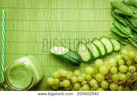 Ingredients for Green detox smoothie. Spinach, grape, cucumber on green background. Flat lay with place for text. Vegan and healthy food concept