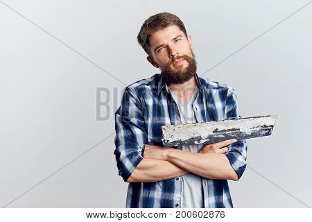 A man with a beard on a light background holds construction tools for repair, check shirt.