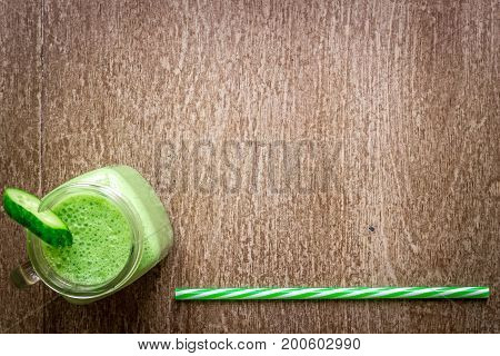 Glass of spinach juice on wooden background. Flat lay with place for text. Vegan and healthy food concept