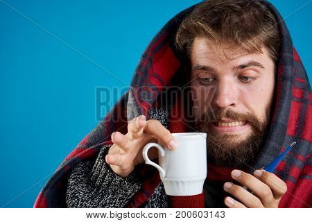 Man with a beard on a blue background in a rug holds a mug, portrait, sickness, sick, flu.