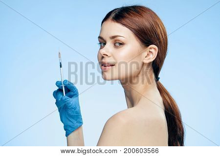 Beautiful young woman in rubber gloves holds a syringe against a blue background, portrait, medicine, plastic surgery.
