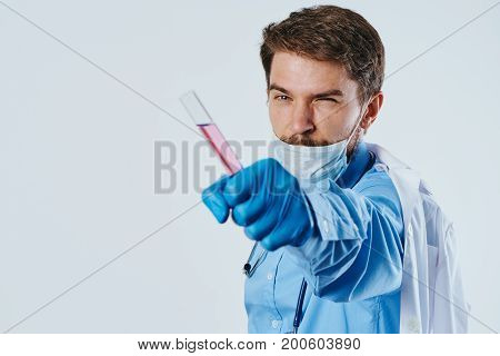 Laboratory assistant in medical clothes holds a test tube with rose liquid, chemistry.