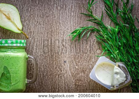 Healthy green smoothie with spinach in a mug against on wooden background. Flat lay with place for text. Vegan and healthy food concept