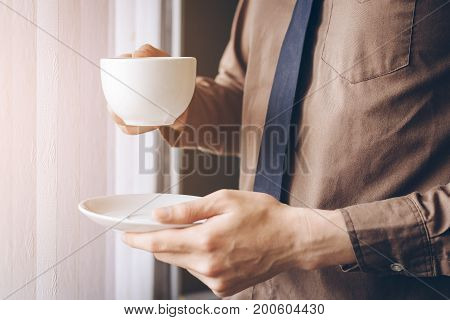 Businessman standing near window and holding coffee cup relax while working.