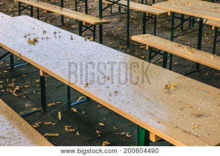 Empty beer garden in fall without guest due to rainy weather. Empty table and benches.