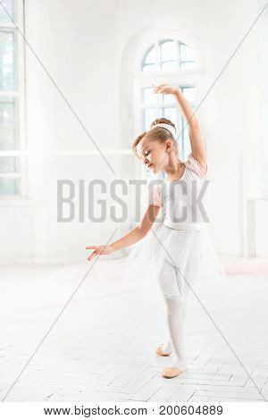 Little ballerina girl in a tutu. Adorable child dancing classical ballet in a white studio. Children dance. Kids performing. Young gifted dancer in a class. Preschool kid taking art lessons.