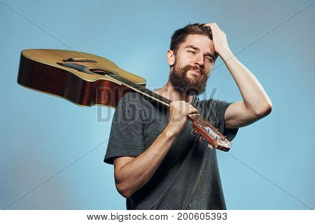Man with a beard on a light blue background holds a guitar, musical instruments.