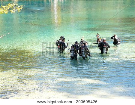 PONCE DE LEON, FLORIDA-OCTOBER 21, 2016: A group of men wearing wet suits and carrying air tanks on their backs are receiving scuba diving instruction at Morrison Springs Park, near Ponce De Leon, Florida.