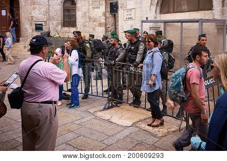 JERUSALEM, ISRAEL - April 15, 2017: Tourists are taking photos with themselves and Israeli police on duty on Via Dolorosa street in The Old City.
