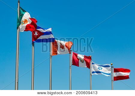A group of flags waving on flag poles from the countries of Austria, Canada, Cuba, Israel, Mexico, and Peru.