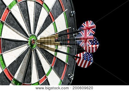 Metal darts have hit the red bullseye on a dart board. Darts Game. Darts arrow in the target center darts in bull's eye close up. Success hitting