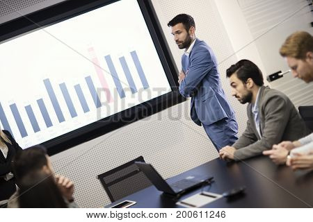 Young attractive businessman showing presentation to his colleagues in conference room