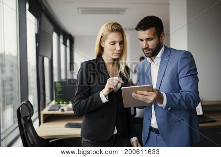 Portrait of attractive business partners using tablet in office