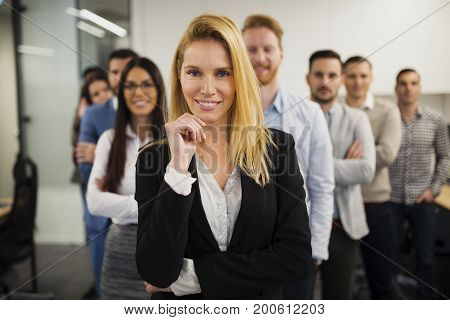 Business lady with positive look and cheerful smile posing for camera in front of her colleagues