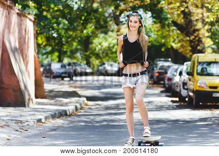 Lovely Blond Girl Riding On Her Skateboard Along The Street