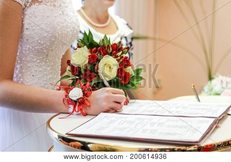 bride puts signature in registry office, wedding day