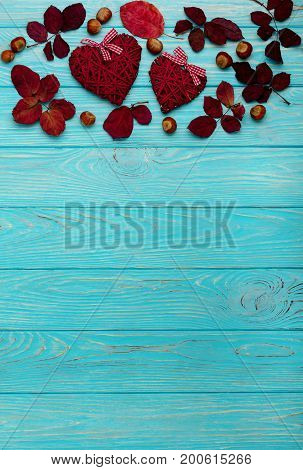 Flat lay frame of autumn crimson leaves walnuts and decorative wicker hearts on a wooden background of azure color. Selective focus.