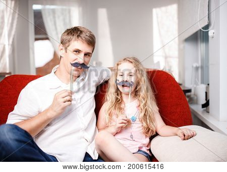 Joyful father and daughter with artificial mustache while sitting togheter on red chair at home