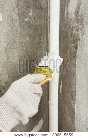 hand painting pipe of radiator central heating with brush during repair