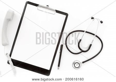 Call doctor. Phone, clip pad and stethoscope on white background top view.