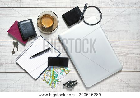 View of a wooden table with a laptop, external hdd, usb cable, mobile, notebook, pen, watch, wallet, passport, map, keys and a cup of coffee on it