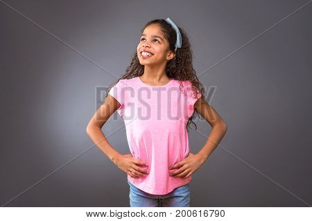 A young black teenage girl standing and looking around while having a big smile