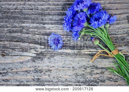 Cornflower Blue Flowers (centaurea Cyanus) On An Old Wooden Table. Top View.