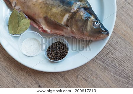 Carp With Scales Peeled And Prepared For Cooking, With Spices On A White Plate.
