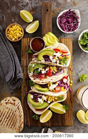 Pulled pork tacos with red cabbage, tomatoes, corn, feta and avocados overhead shot