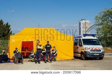 STRASBOURG FRANCE - APR 28 2017: Premier Secours - First Aid van parked on the city street with safety workers surveying the zone nearby public open space event