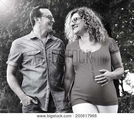 Pregnant walking couple on garden background.