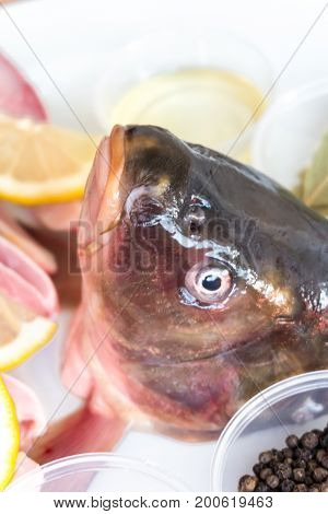 The Head Of A Carp Looking At The Camera Next To The Carp Fillet And Spices On A White Plate.
