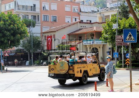 Alanya, Turkey, July 2017: tourists in a 4WD jeep excursion ride down the city street.
