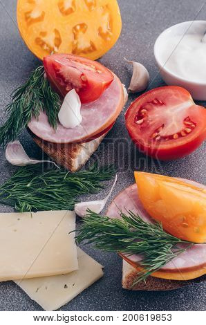Sandwiches with ham tomato and cheese on a dry surface