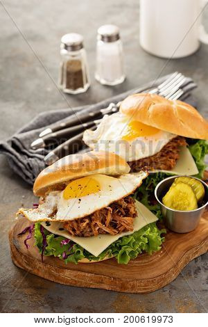 Pulled pork breakfast sandwiches with fried egg, cheese and lettuce