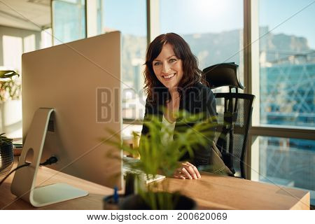Portrait of beautiful female entrepreneur sitting at her desk with desktop computer looking at camera and smiling. Caucasian young woman at her workplace.